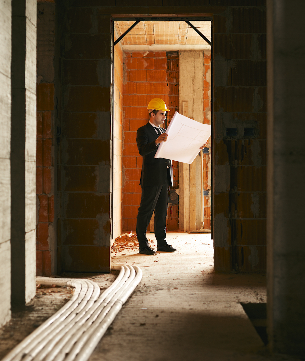 Architect standing in house under construction with building plan
